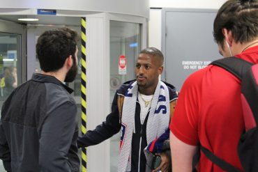 FC Dallas winger Fafa Picault speaks with FC Dallas team administrator Juan Gonzalez after arriving at DFW Airport on 1/15/20 (Dan Crooke)