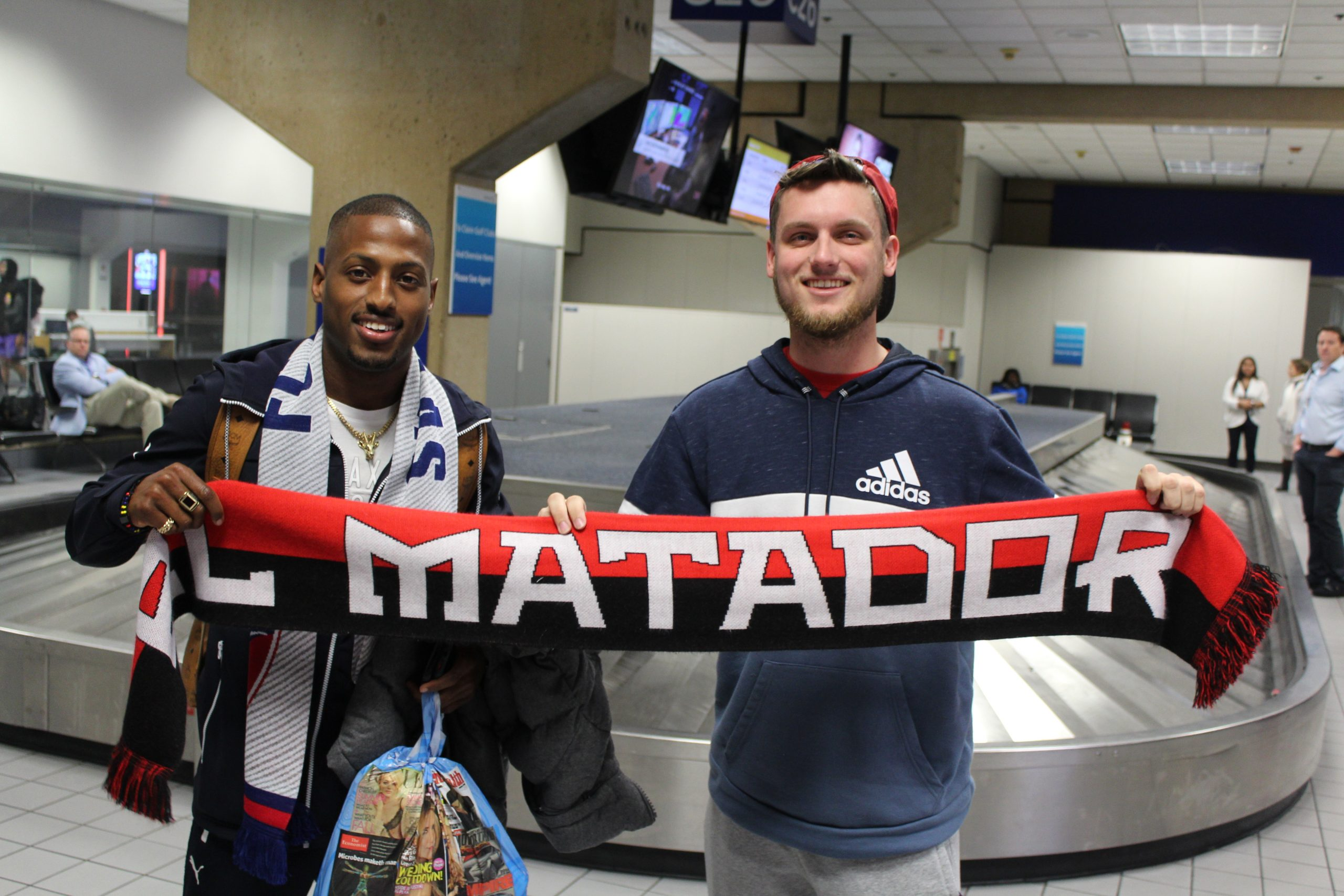FC Dallas winger Fafa Picault holds an El Matador Scarf with FC Dallas fan Luis Dollar after arriving at DFW Airport on 1/15/20 (Dan Crooke)